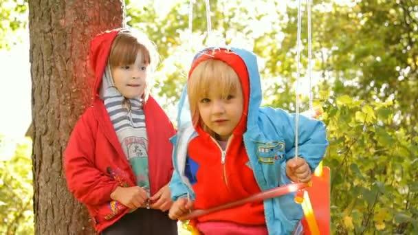 dvě dívky hrát, směje se na houpačce