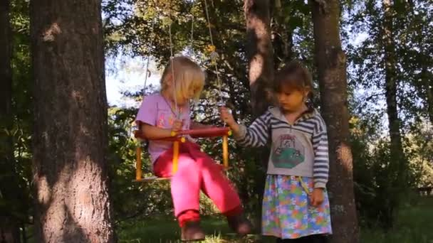Two girls playing, laughing on a swing