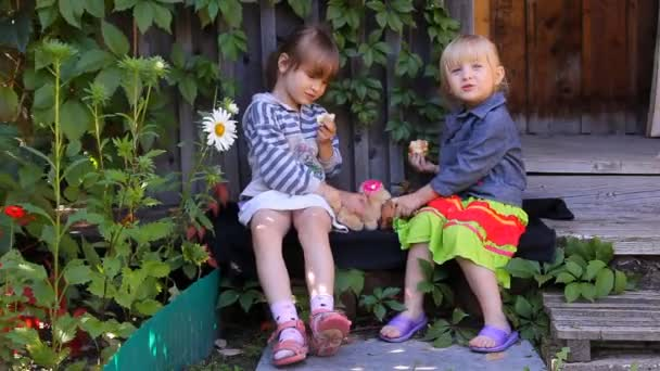 Two girls eating apples, playing dogs toys