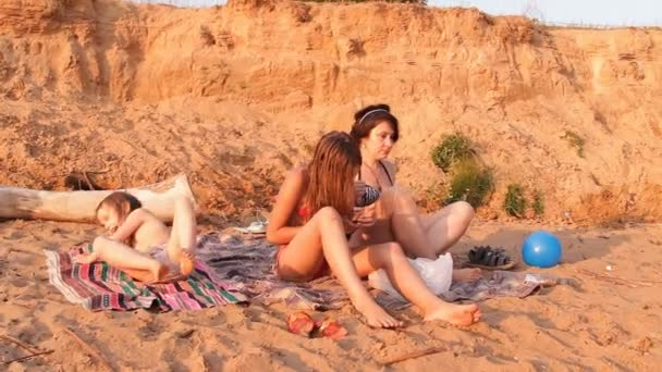 The mother and the two girls on the beach, a woman makes massage