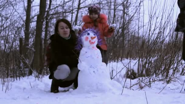 Woman (mother) and a little girl playing with snowman