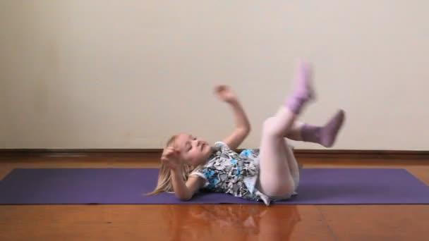 una bambina gioca il pazzo, facendo esercizi, yoga