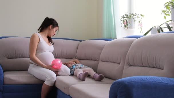 těhotná žena a dívka si hraje s míčem