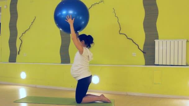 těhotná žena, která dělá cvičení s míčem, jóga