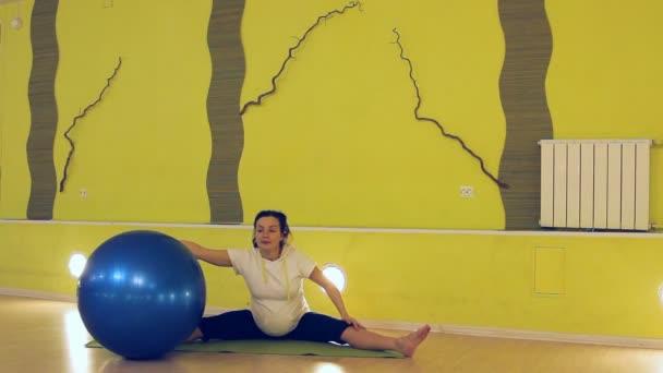 eine schwangere Frau macht Übungen mit dem Ball, Yoga