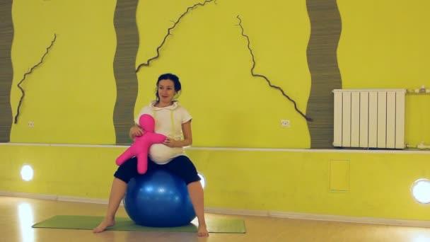 těhotná žena s panenkou dělá cvičení s míčem, jóga