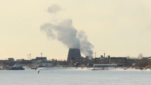 lyžař jede na pozadí továrních komínů a kouře