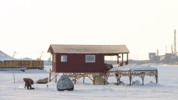 zimní rybolov na pozadí továrních komínů, jeřáby