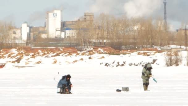 zimní rybolov na pozadí továrních komínů