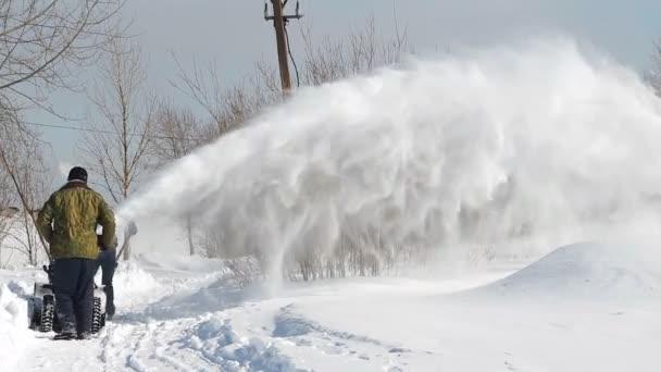 Männer schaufeln Schneemaschine und Schaufel