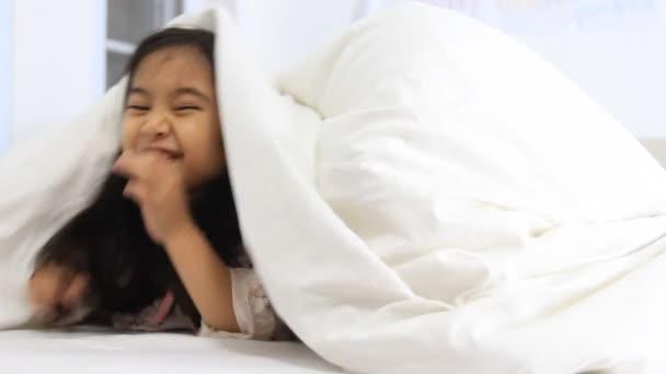 malé asijské dívky hrát na schovávanou na postel