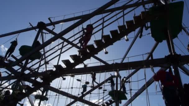 Families play on large gorilla climb ropes course silhouette 2