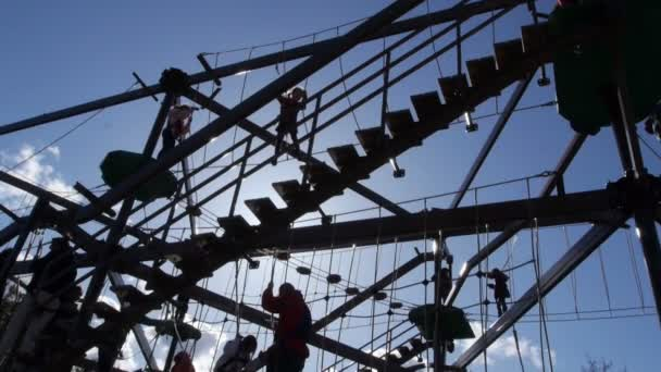 Families play on large gorilla climb ropes course silhouette 1