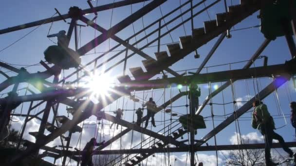 Families play on large gorilla climb ropes course silhouette 3