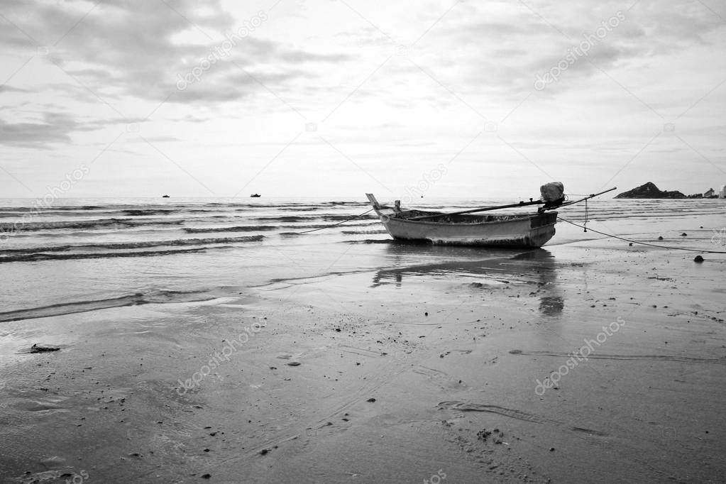Old fishing boat landing on the beach. Black and white.