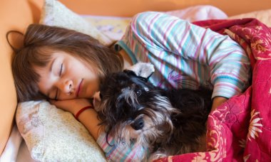 Girl with dog in bed