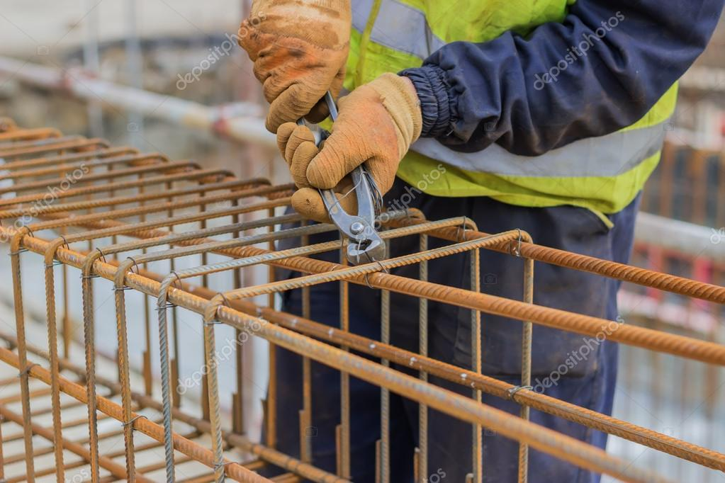 workers hands using steel wire and pincers to secure rebar stock photo