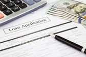 Photo Loan application form and dollar banknotes