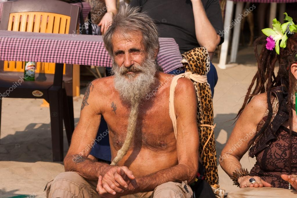 An unidentified older man with a beard sits at the annual festival of Freaks, Arambol beach, Goa, India