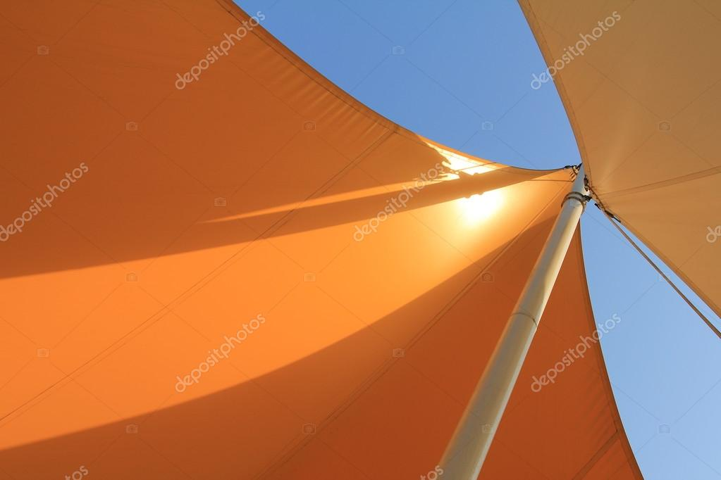 Overhead awnings on a pole against blue sky