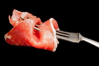 Delicious parma ham on fork.