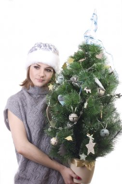 Pretty girl in hat near Christmas tree Snow Maiden with a gray teddy bear in her arms on a white background