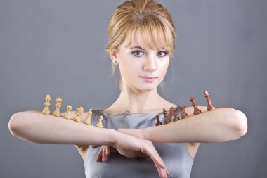 Beautiful young girl holding chess pieces in hand on gray background