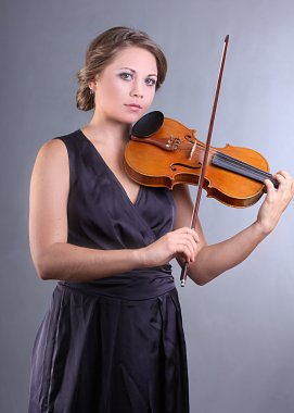 A charming young girl playing the violin professionally
