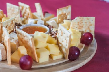 different varieties of cheese with grapes, crackers, nuts and ho
