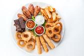 Fotografia grigliate, formaggi, crostini e salse su un piatto rotondo su ba bianco