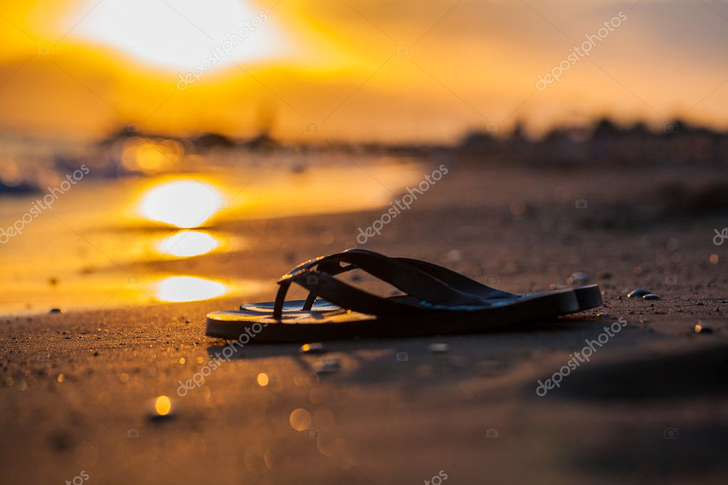 Sandals on the seashore and sunset