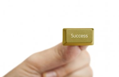 Hand holding golden success computer key