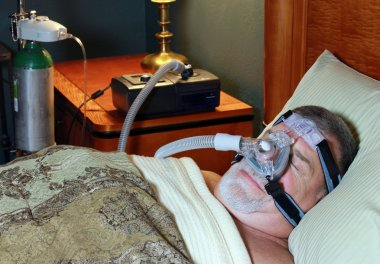 Senior Adult Wearing CPAP in Bed with Oxygen