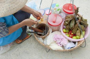 Thai woman cooks a traditional salad on a street on Samet Island, Thailand.