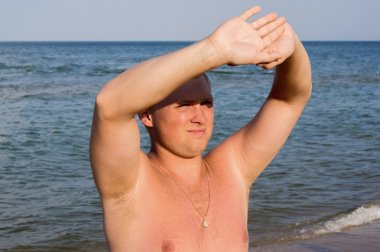 Nice guy squinting in the sun on beach