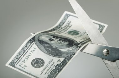 Scissors cutting a dollar bill in half