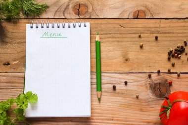 Notebook for recipes with green pencil, fresh herbs, spices and tomato on old wooden table
