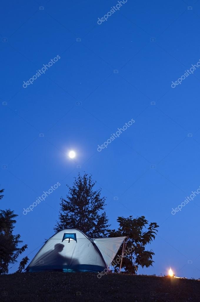 C&ing in tent with human shadow and c&fire moon and stars on the clear blue sky u2014 Photo by Sziban & Tent in twilight with moon and fire vertical u2014 Stock Photo ...