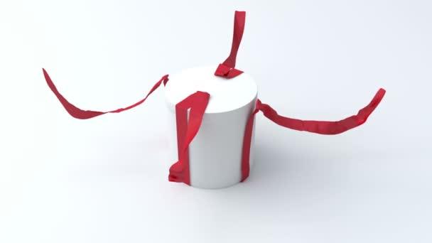 bílý dárek ve tvaru válce s červenou mašlí, otevření