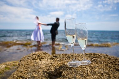 Theme wedding - the bride and groom on the sea holding hands, in the foreground champagne glasses