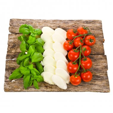 Ripe tomatoes and mozzarella balls garnished with basil Italian food ingredients forming the italian flag on the old board isolated on white background