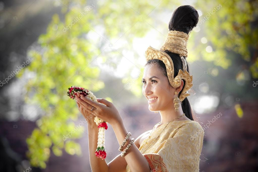Woman wearing typical thai dress with thai style temple background
