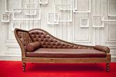 hnědý gauč na červeném koberci