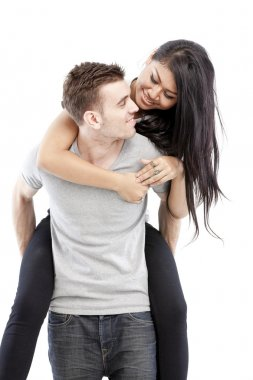 Portrait of a happy young man giving a piggyback ride to her girlfriend against white background