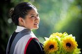 junge Absolventin mit gelben Blumen