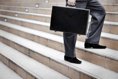 Businessman standing with a briefcase,outdoor.