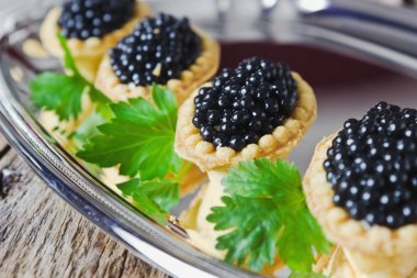 cake with black caviar and parsley