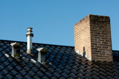 Steel roof with ventilation pipes, flue terminal and chimney in
