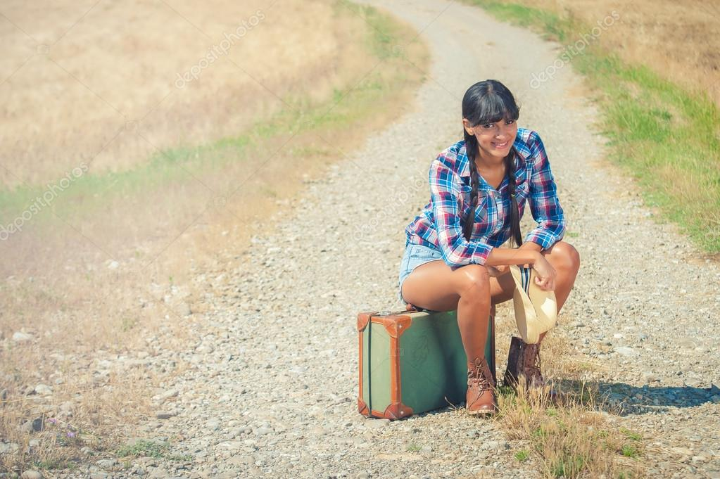 Beautiful brazilian woman with a suitcase on a road trip.