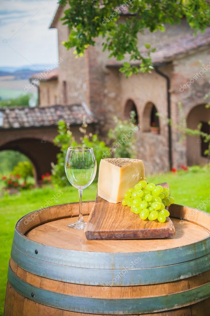 Cheese and grapes on a barrel in the Tuscan landscape Italy